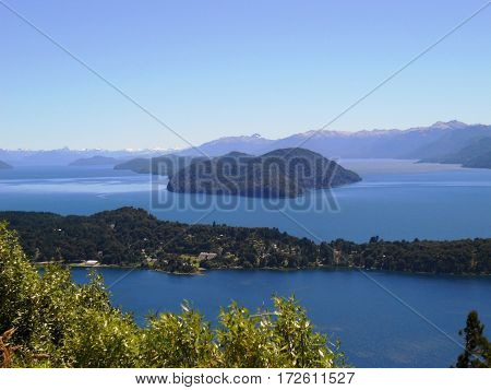 Beautiful landscape of mountains and lakes behind the leaves of a tree in Neuquen, Argentina.