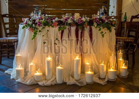 Many candles in vases around the banquet table