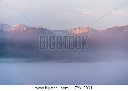 Spring landscape with morning fog in a mountain valley. Beautiful morning light. Delicate pastel range of photos. Carpathians, Ukraine, Europe. View of the ridge Chornohora