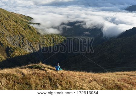 Man tourist sitting on a hill and looks at valley. Beautiful clouds over the mountains. Autumn landscape on a sunny morning. Zemo Svaneti, Georgia