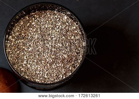 Close-up Chia seeds in black cup and dark background. Concept of detox and healthy eating. For backdrop, substrate, composition use. Top view. Lots of place for writing text around it