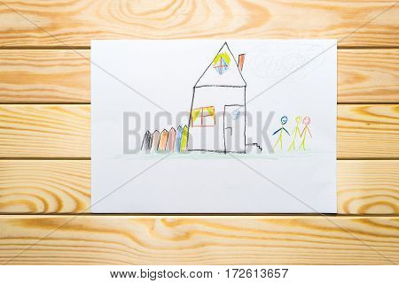 child's drawing. home and happy family wooden background