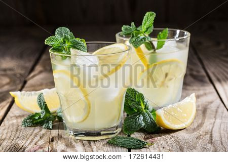 homemade lemonade with fresh lemon and mint on a wooden background