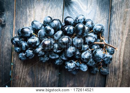 Bunch of black grapes on a shabby wooden background. Top view