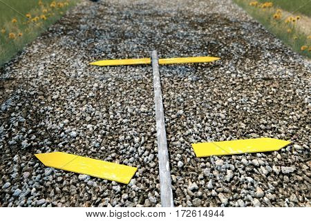 3d rendering of yellow signpost laying on the gravel ground of footpath