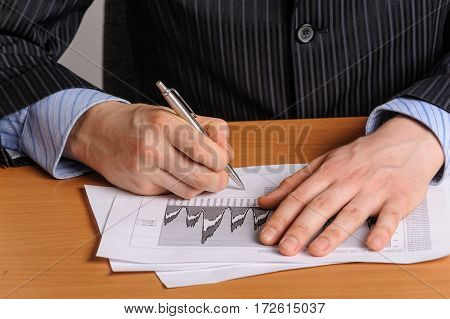 Businessman with pen analysing the financial bar chart
