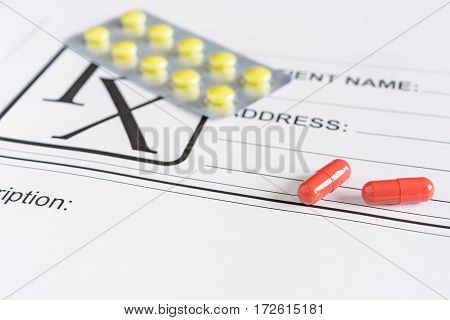Medical prescription form with pills over it