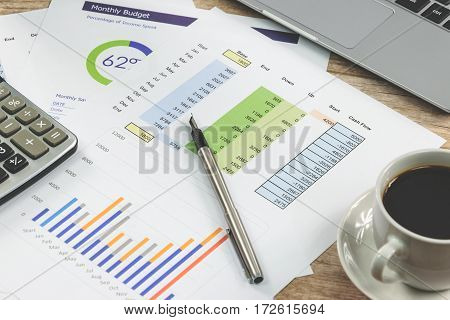 Modern workplace at the office: printouts of charts and financial data next to a laptop cup of coffee and calculator on the desk (reduced tone)