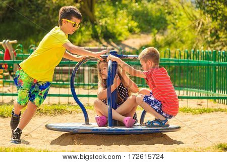 Joyful active childhood. Playful kids playing on playground. Children having fun in summer. Young tourists spending actively time.