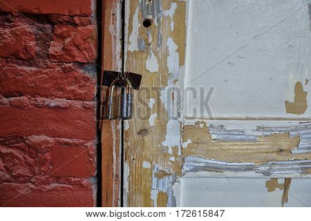 Old white door closed on padlock. The paint on the door crumbled.