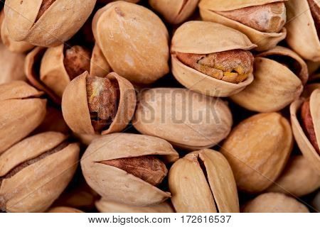 Salted pistachios in a lot of close-ups. Background.