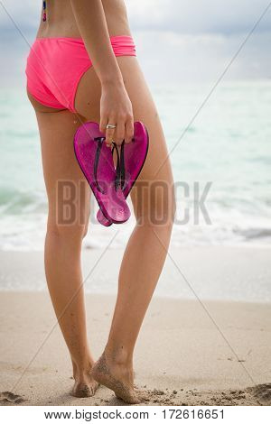 Slim girl in pink bikini standing on the white sandy beach near the ocean and holding flip flops. Strong and fit woman on the beach going to swim in the sea. Active healthy and slim. Lifestyle concept