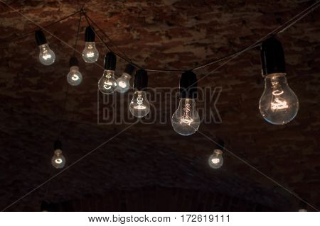 Several light bulbs hanging and shines on the background of an old brick ceiling