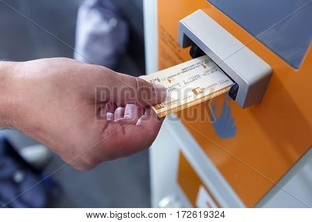 BARCELONA/ SPAIN - AUGUST 6, 2016: A man validating ticket in a punching machine for the train. Barcelona, Spain.