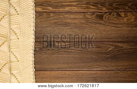 Knitted white blanket on a wooden background with copy space