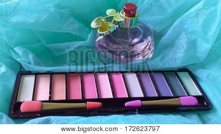 Colorful set of cosmetics, makeup brushes, hair brush and perfume bottle