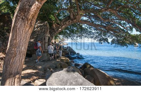 A group of people walking on a rough trail by the shore