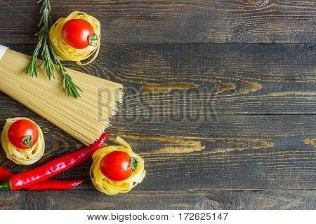 Pasta with tomato chili peppers rosemary on wooden table. Top view