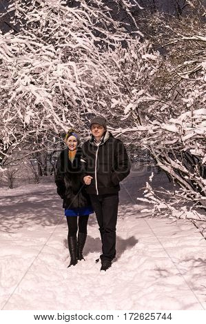 Loving couple walking in winter snow-covered park at night by the light of lanterns