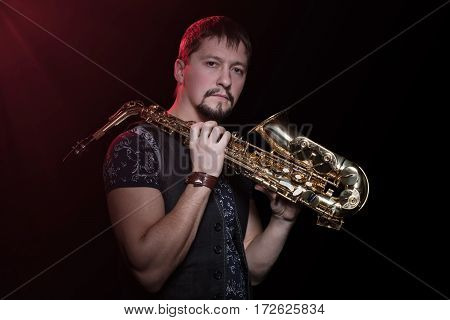 Serious bearded saxophonist with sax on the shoulder isolated against a black background