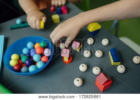 Cropped image of children playing with blocks and beads