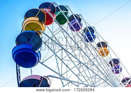old Ferris wheel with colored cabins open against the blue sky