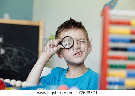 Curious schoolboy looking through a magnifying glass