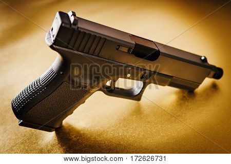 one black handgun on a shiny gold background