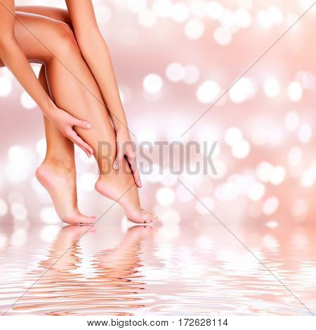 Beautiful woman legs on an abstract background with blurred lights