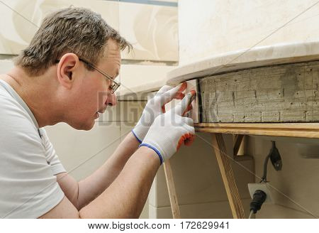 Worker is puting the piece of tile on the curved wall under a sink.