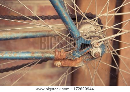 Rusty old Bicycle wheel with a chain. Brown background