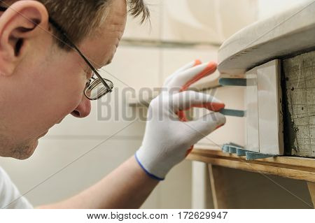 Worker is propping tile on the curved wall using plastic wedges.