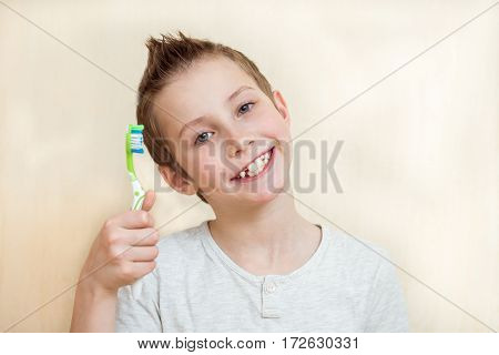 Cute boy shows his teeth and toothbrush. Light background