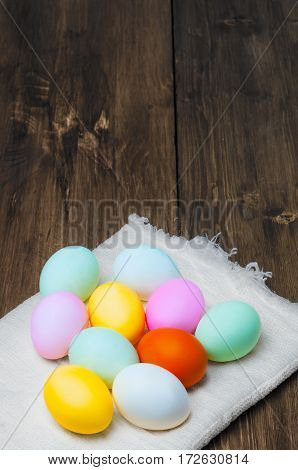 Colorful Easter eggs on vintage towel on old wooden table, rustic background, holiday concept. Textspace, copyspace. Darken scene, low key.