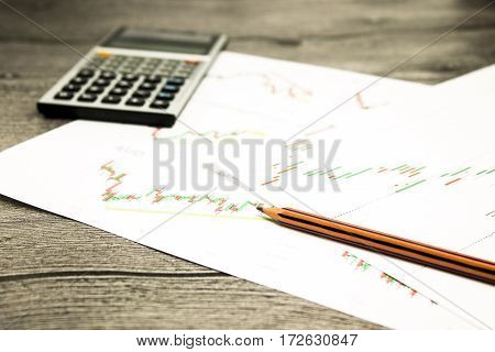 calculator and pencil on graffica the Dow Jones on forex market at grey table