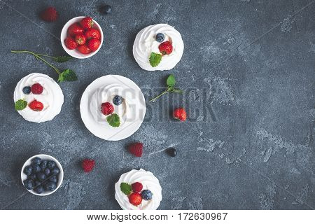 Meringues Pavlova cakes with strawberry and blueberry on dark background. Sweet dessert. Flat lay top view