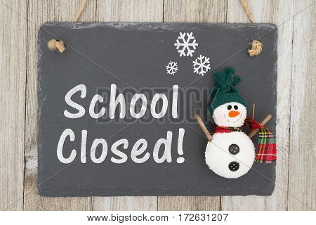 School canceled sign A chalkboard sign with a snowman with text School Closed on weathered wood