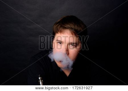 Young Adult Male Vaping In Low Key