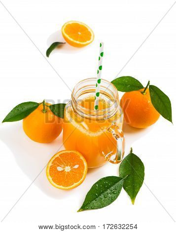 Composition with orange juice and orange fruits with green leaves isolated on white background.