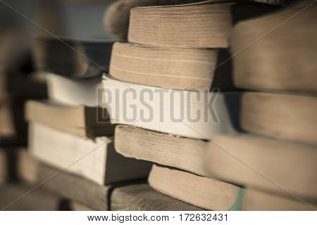 Piles of old paperback book by the beach held down with stones from the wind.