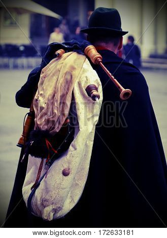 bagpiper with an old black cape and the bagpipes on the shoulders