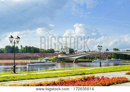 VELIKY NOVGOROD RUSSIA - AUGUST 5 2016. Novgorod Kremlin with footbridge and pleasure boat floating the Volkhov river, Veliky Novgorod, Russia
