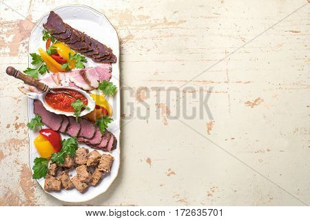 plate of meat delicacies of wild boar, wild duck, elk, hare. on wooden background, top view with copy space.