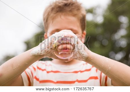 Portrait of adorable kid boy making soap bubble with his hands outdoors. Child blowing soap bubbles. experiments and experiences. Children activities outdoors. Vacations.