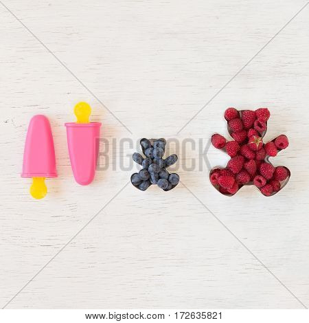 Teddy bear shaped molds for the cookies full of fresh organic raspberries and pink popsicle forms for sorbet onwhite wooden background.