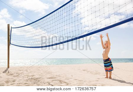 Cute kid boy on background volleyball net and sunny ocean beach. Child standing on beach volleyball court and having fun. Vacations by sea. Sport activities for children outdoors. Sport and leisure