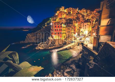Colorful Italian Illuminations and Reflections. Riomaggiore Village at Night. La Spezia Region. Liguria Italy.