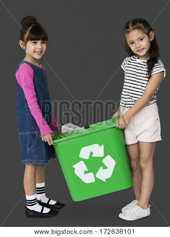 Two girls are holding a recycle bin