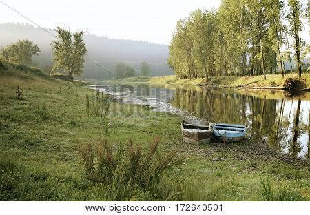 Two Boats On The Shore Of Small River In Summer