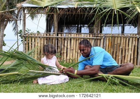 Indigenous Fijian man teach young tourist girl how to create a basket from weaving a Coconut Palm leaves.Travel Fiji concept Real people copy space poster